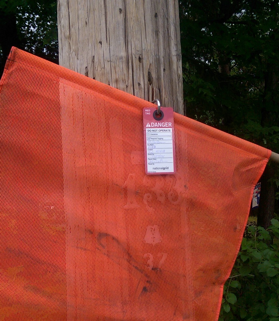 Close up of orange flag on utility pole, along with tag with lock-out information