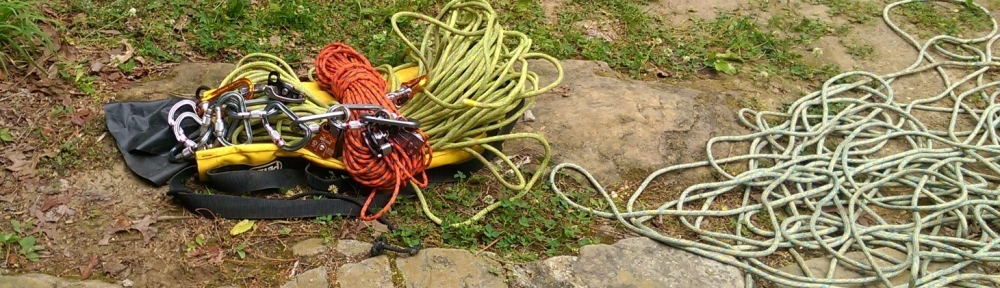 Pile of caving rope on right, pile of random carabiners, ropes, etc on left