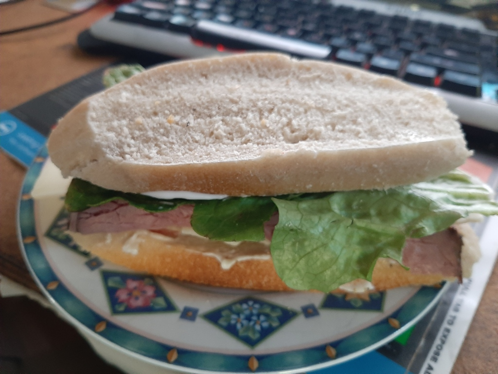 A roast beef sandwich with lettuce and tomato and mayo on a plate. In the background is a keyboard.