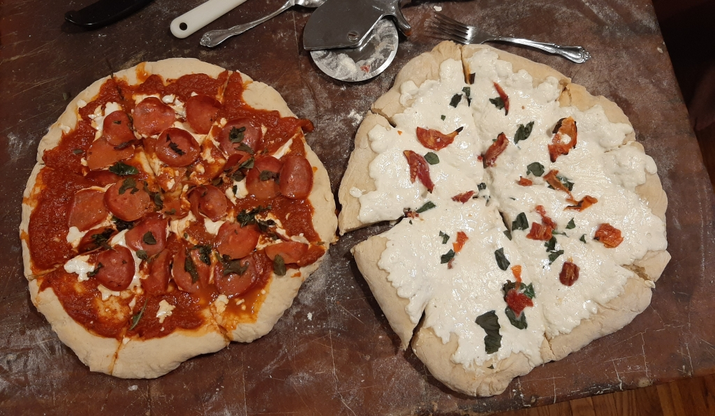 An image of two pizzas from above, resting on a butcher block. The one on the left is a pepperoni pizza. The one on the right is a white pizza with sundried tomatoes.  Both have fresh basil from my garden on them.