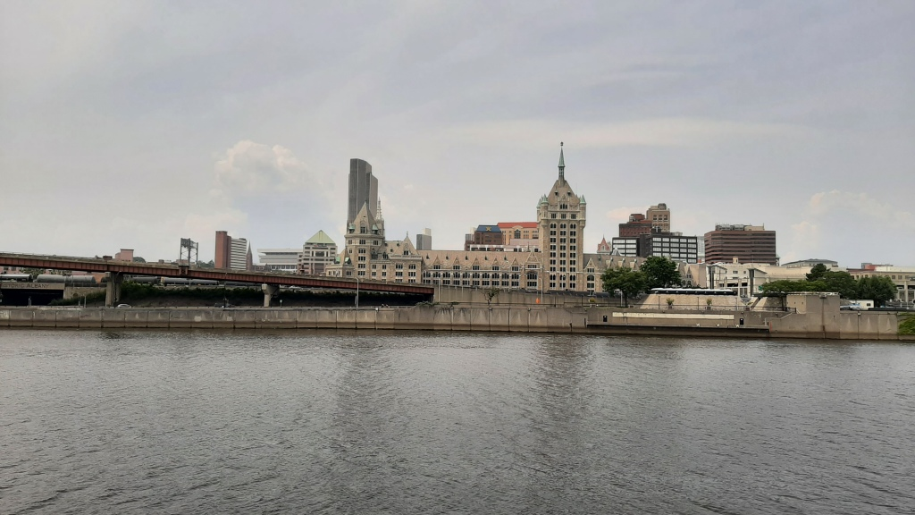 River in foreground, with the old D&H building in the midground and Corning Tower left of center in the background.