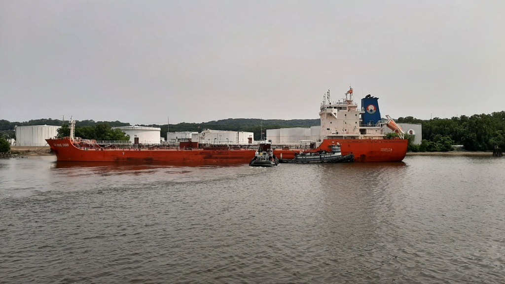 Large orange tank, with two tugboats pushing it into position.