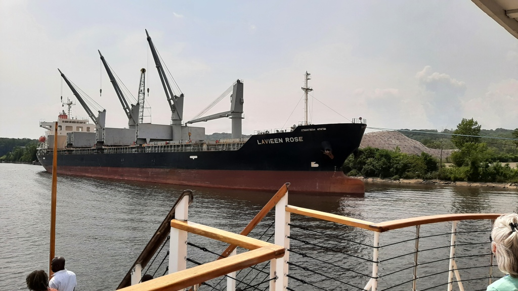 Bulk cargo ship with 3 of 4 cranes in operation, loading scrap