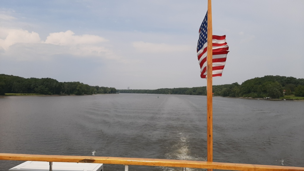 Image is of the Hudson, with the Corning tower a speck in the background. Boat ensign in the foreground.
